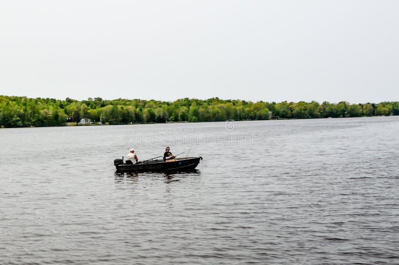 Pescatori in barca a motore, che pescano sul lago fotografie stock libere da diritti
