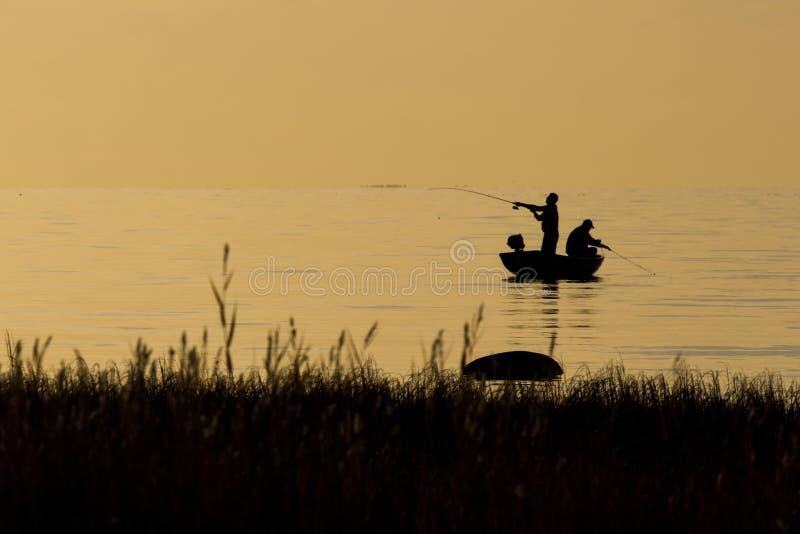 Pescatori che pescano sulla spiaggia durante al tramonto fotografie stock libere da diritti