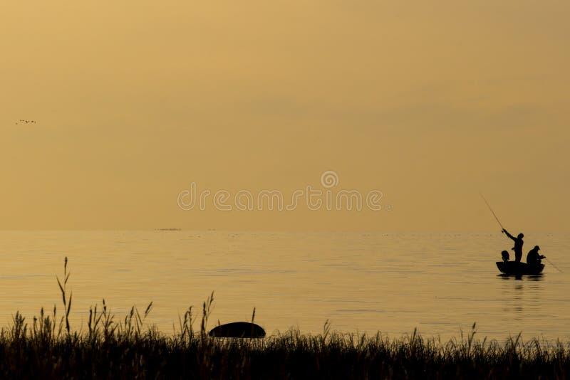 Pescatori che pescano sulla spiaggia durante al tramonto fotografie stock
