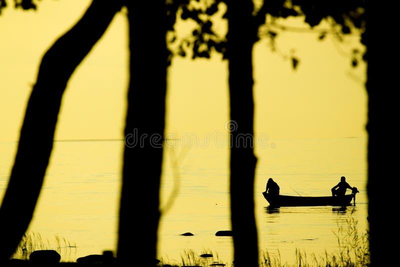 Pescatori che pescano sulla spiaggia durante al tramonto fotografia stock libera da diritti