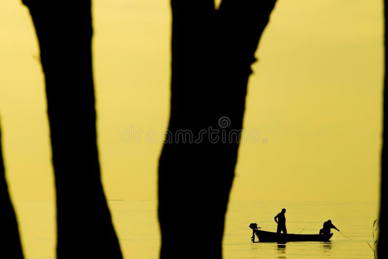 Pescatori che pescano sulla spiaggia durante al tramonto immagini stock libere da diritti