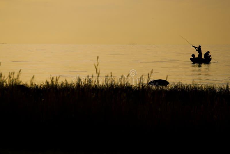 Pescatori che pescano sulla spiaggia durante al tramonto immagini stock