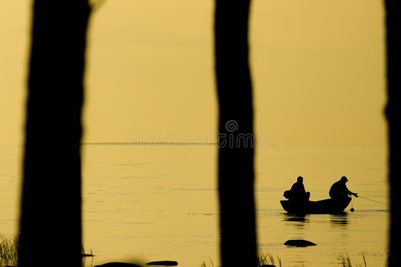 Pescatori che pescano sulla spiaggia durante al tramonto fotografia stock