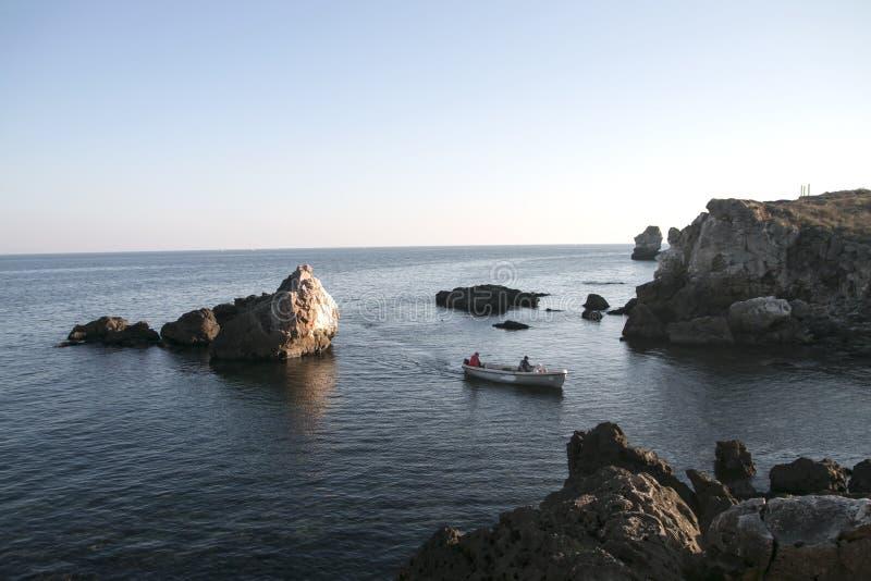 Pescatori che ritornano a casa con la barca nel tramonto fotografia stock libera da diritti