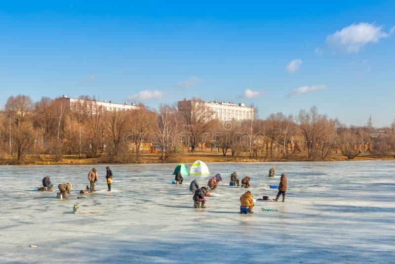 Pescatori che si siedono e che camminano sul ghiaccio fotografia stock libera da diritti