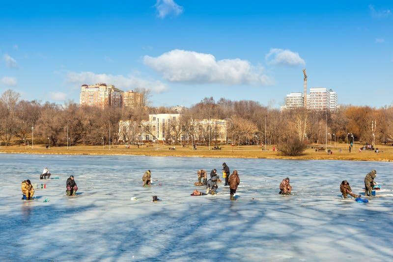 Pescatori che si siedono e che camminano sul ghiaccio fotografia stock
