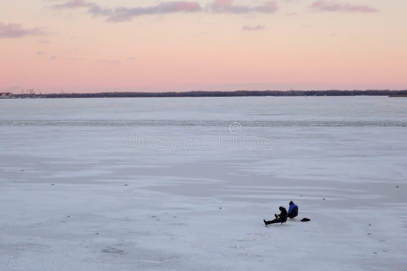 Pescatori che si siedono su un fiume congelato ad un giorno gelido di bello tramonto Pesca di inverno sul fiume Volga fotografie stock