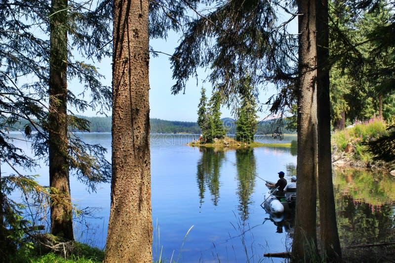 Pescatori con una barca nel lago della montagna fotografia stock