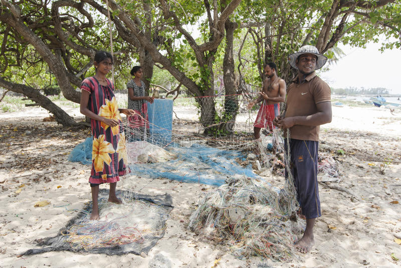 Pescatori e donne che preparano le loro reti da pesca sull'isola di Delft nella regione settentrionale di Jaffna nello Sri Lanka fotografie stock