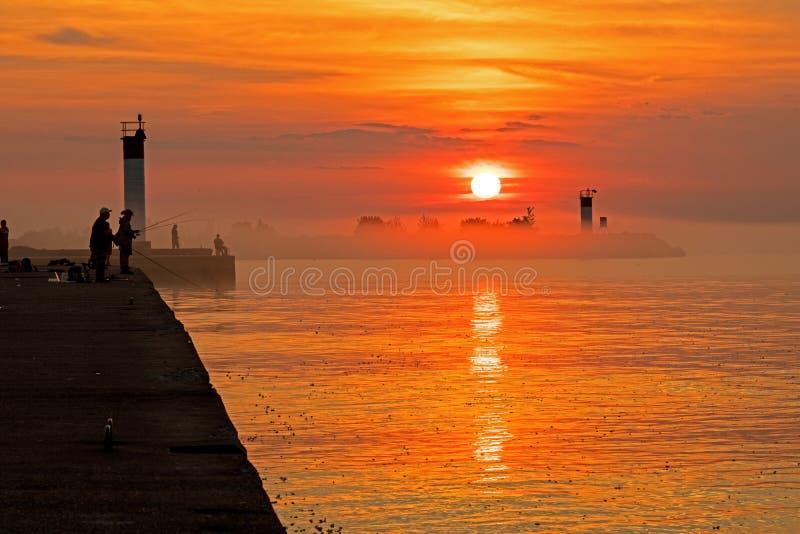 Pescatori su Pier At Sunrise On Lake Ontario fotografia stock libera da diritti