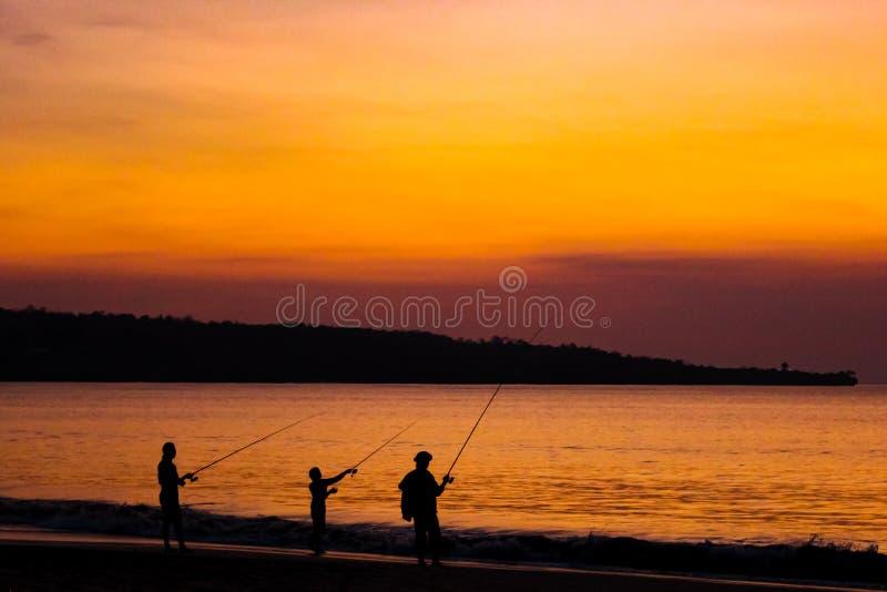 Pescatori sulla spiaggia sull'isola di Bali al tramonto immagini stock