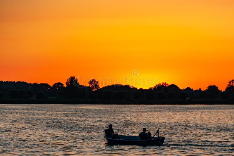 Pescatori in una piccola barca durante il tramonto sui plas di Zoetermeerse del lago immagini stock