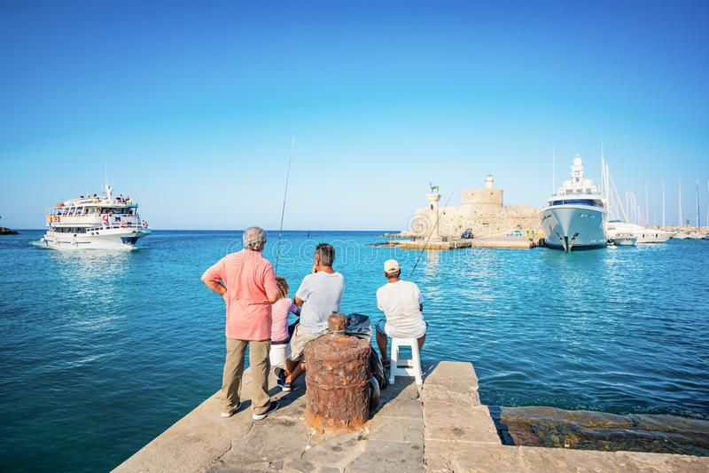 Pescatori vicino all'entrata nel porto di Mandraki in città di Rodi immagine stock
