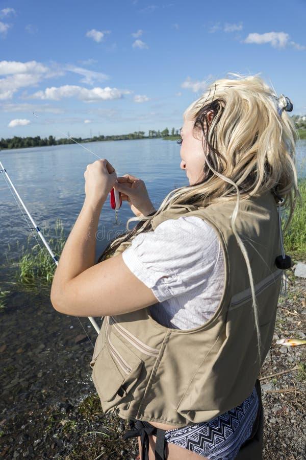 Pescatrice che appende il suo richiamo immagine stock