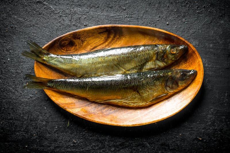 Pesce affumicato su un piatto di legno immagini stock libere da diritti