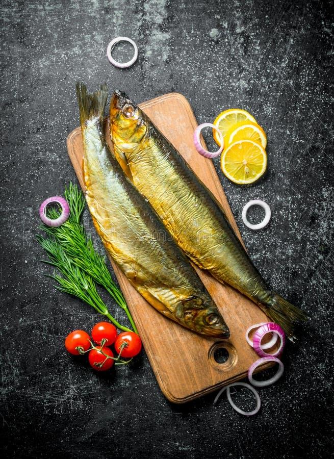 Pesce affumicato su un tagliere di legno con le fette dei pomodori, dell'aneto e del limone fotografia stock