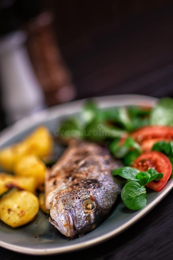 Pesce al forno di Dorado con le verdure nel forno su un fondo scuro immagine stock