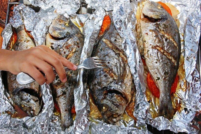 Pesce al forno di dorado quattro in stagnola con le verdure per una cena di festa della famiglia, una mano dei bambini con una fo fotografie stock
