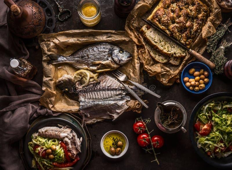 Pesce al forno di dorado sulla tavola scura con l'insalatiera, il pane di focaccia, i pomodori e le olive, vista superiore Pranzo fotografia stock