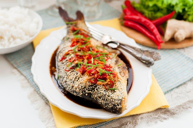 Pesce al forno di stile asiatico con il condimento della salsa del peperoncino rosso, dello zenzero e di soia fotografia stock