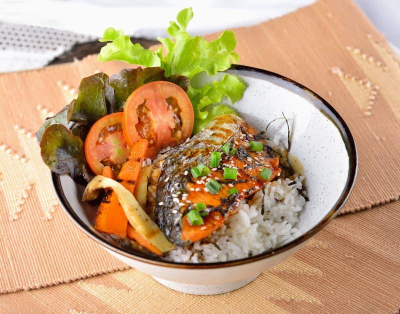 Pesce arrostito con riso, salsa di soia su fondo di legno fotografia stock
