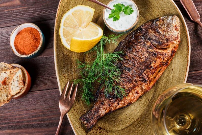 Pesce arrostito di dorado con il limone e verdi sul piatto su fondo di legno fotografia stock libera da diritti