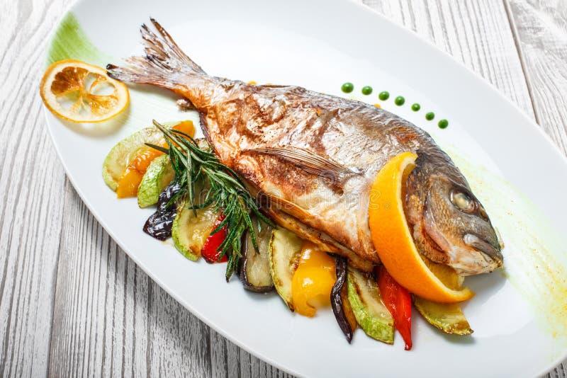 Pesce arrostito di dorado con le verdure al forno ed i rosmarini sul piatto sulla fine di legno del fondo su fotografia stock libera da diritti