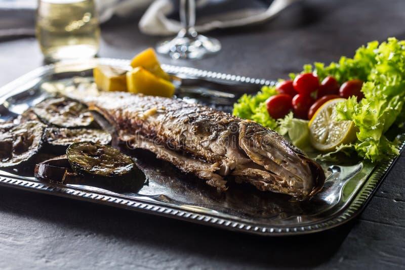 Pesce arrostito sul piatto con la verdura fresca e arrostita fotografia stock libera da diritti