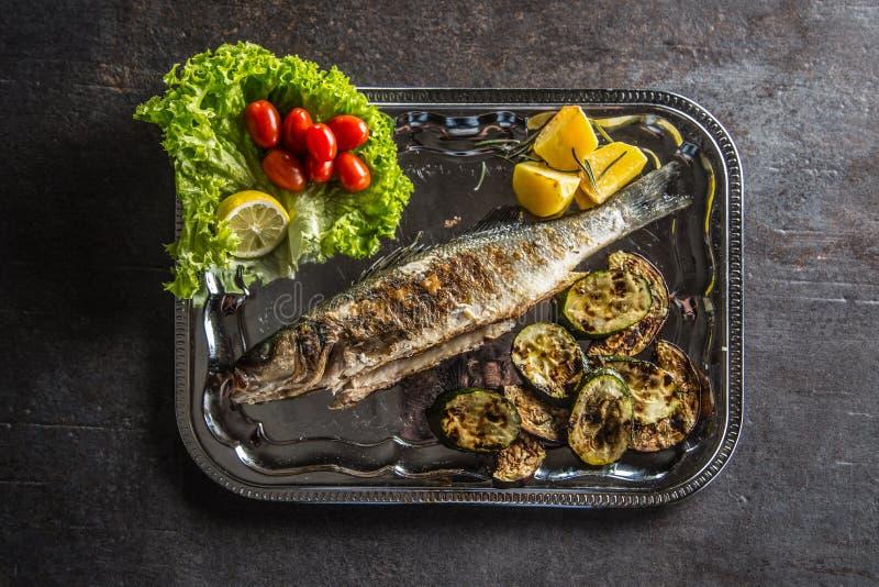Pesce arrostito sul piatto con la verdura fresca e arrostita fotografia stock