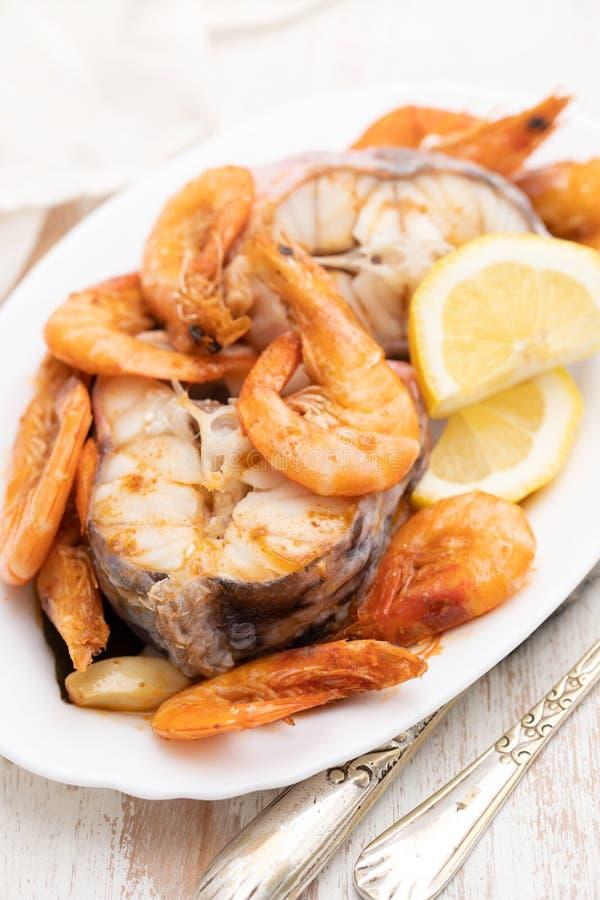 Pesce bollito con i gamberetti ed il limone sul piatto bianco fotografia stock libera da diritti
