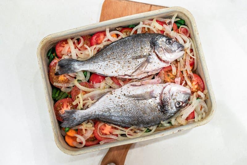 Pesce crudo due, per cuocere sul cuscino di verdure in vassoio bollente del metallo su fondo bianco fotografia stock libera da diritti