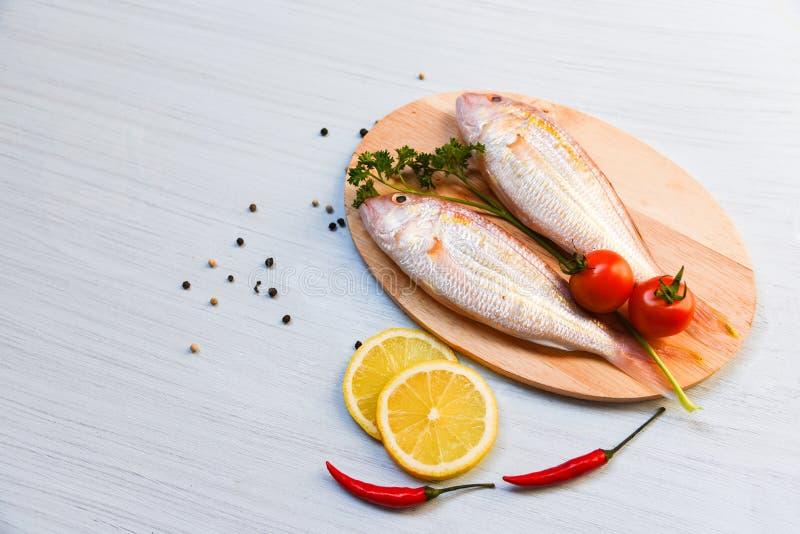 Pesce crudo fresco sul tagliere con i peperoncini rossi del limone del pomodoro ed il prezzemolo verde fotografia stock libera da diritti