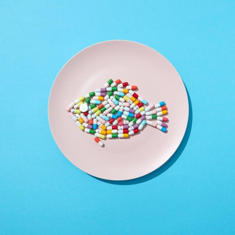 Pesce dalle pillole variopinte e dalle compresse su un piatto bianco su un fondo blu con lo spazio della copia Integratore alimen fotografia stock libera da diritti