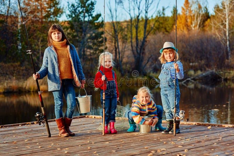 Pesce del fermo di quattro bambine su un pontone di legno Fine settimana nel lago Pescando con gli amici immagine stock libera da diritti