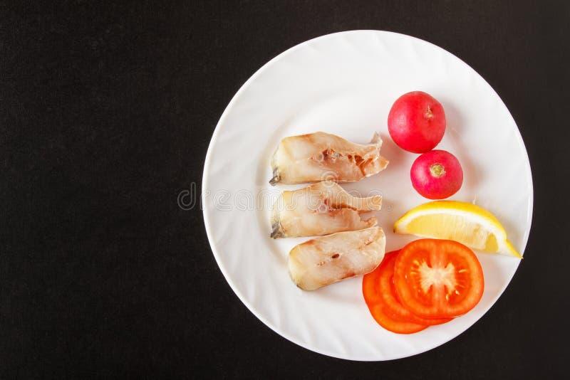 Pesce della bistecca con gli ortaggi freschi sul piatto bianco per la cottura del pranzo Fondo nero con la vista superiore immagine stock