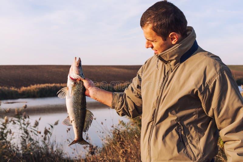 Pesce della tenuta del pescatore fotografia stock libera da diritti