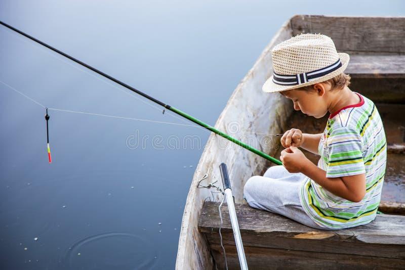 Pesce di cattura del giovane pescatore sulla pesce-barretta fotografia stock libera da diritti