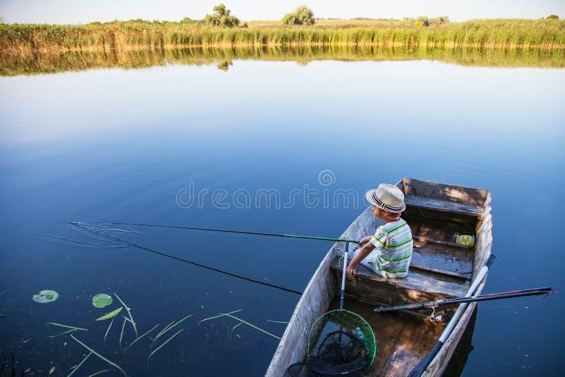 Pesce di cattura del giovane pescatore sulla pesce-barretta immagini stock