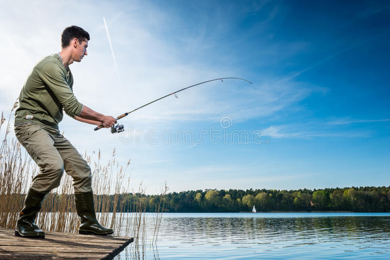 Pesce di cattura del pescatore che si inclina nel lago fotografia stock