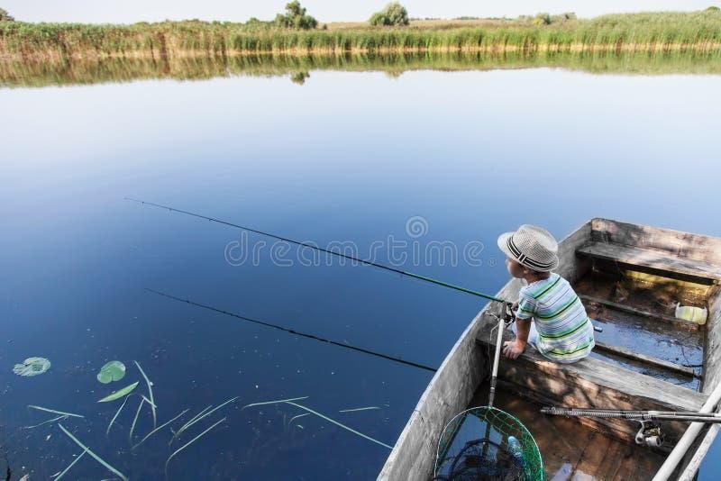 Pesce di cattura del ragazzo sulla pesce-barretta immagini stock libere da diritti