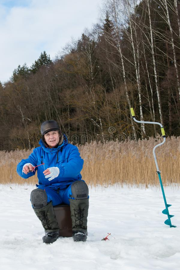 Pesce di cattura di Firsheman sul lago al giorno di freddo di inverno immagini stock