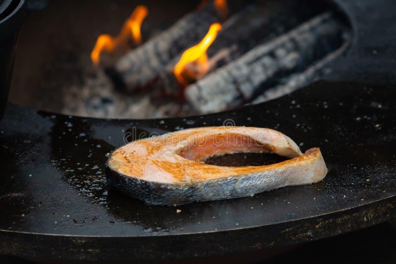 Pesce di color salmone arrostito con le varie verdure sulla griglia ardente immagini stock libere da diritti
