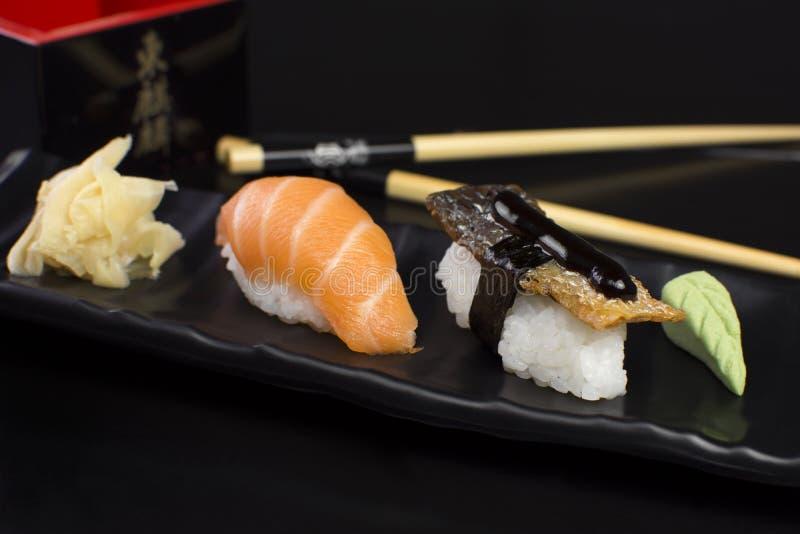 Pesce di color salmone e niguiri di color salmone della pelle in tavola del ristorante immagine stock libera da diritti