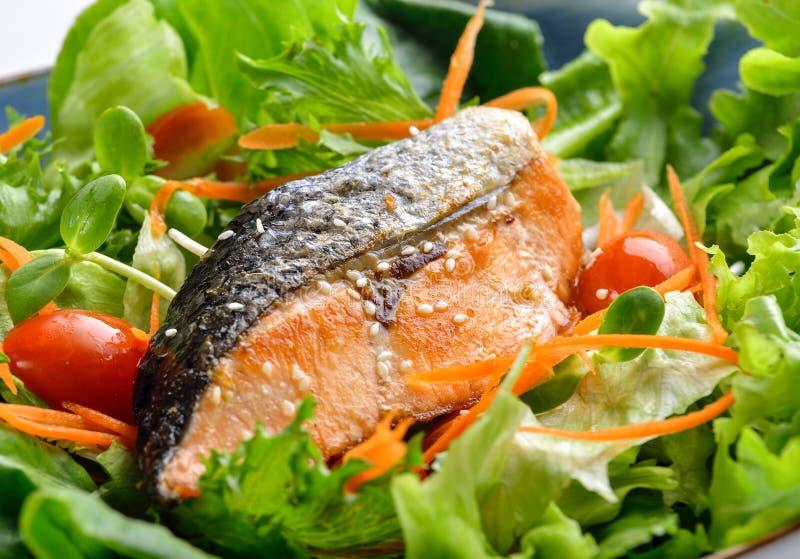 Pesce di color salmone fritto con insalata di verdure su fondo di legno fotografia stock libera da diritti