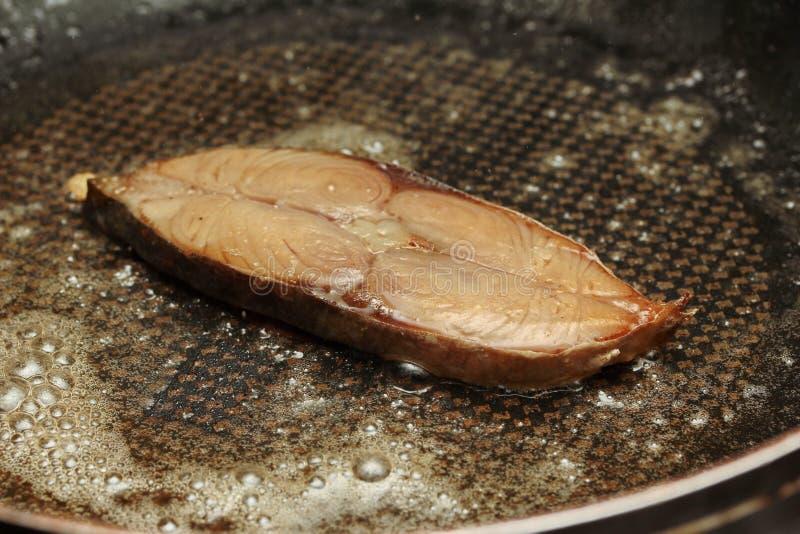 Pesce di mare salato secco fritto in grasso bollente, sgombri macchiati in pentola fotografie stock libere da diritti