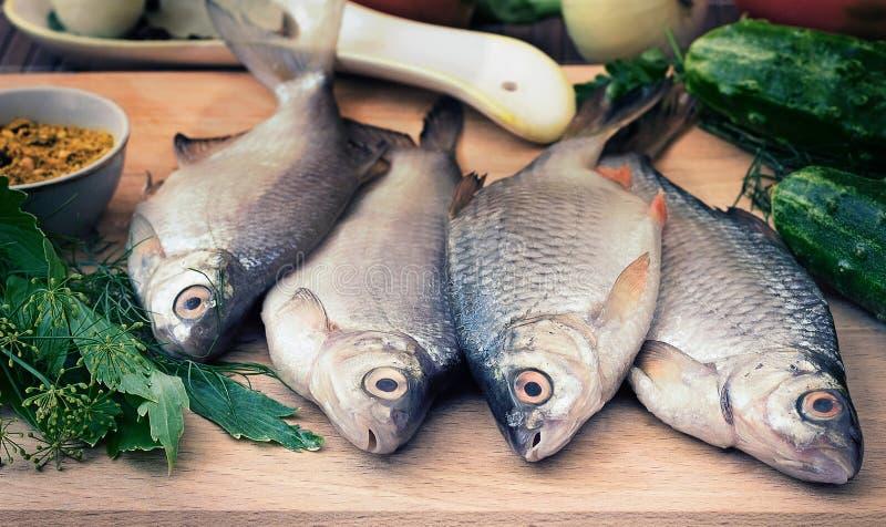 Pesce e componenti per la sua preparazione: verdure, spezie, prezzemolo fotografie stock