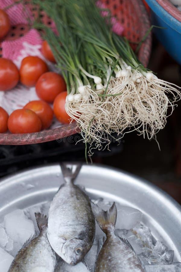Pesce e ortaggi freschi raffreddati con ghiaccio sul contatore fotografia stock