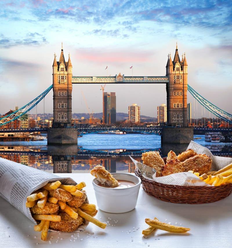 Pesce e patate fritte contro il ponte della torre a Londra, Inghilterra fotografia stock libera da diritti