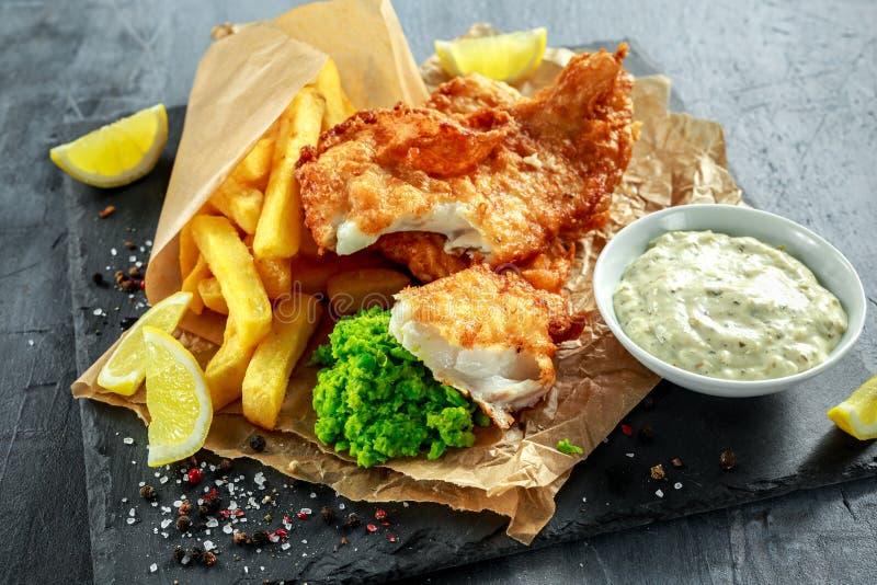 Pesce e patate fritte tradizionale britannico con i piselli schiacciati, salsa di tartaro su carta sgualcita fotografia stock