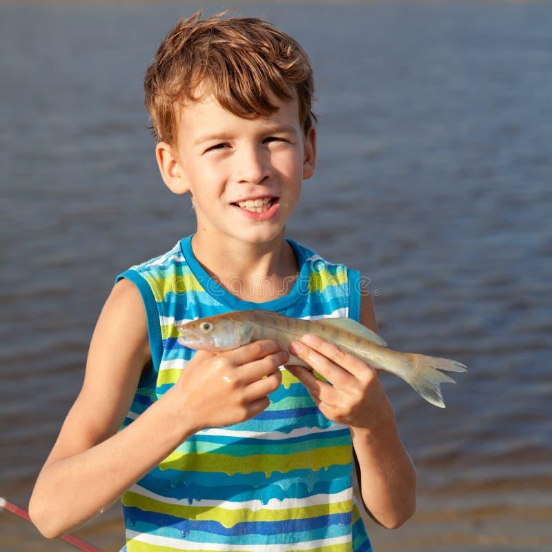 Pesce e sorridere della tenuta del ragazzo fotografia stock libera da diritti